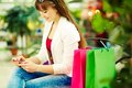 Break after shopping pretty lady with colorful bags sitting in trade center and writing sms Royalty Free Stock Image