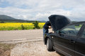 Breakdown on the road man with his car parked beside for a mechanical problem canola field in background Royalty Free Stock Photos