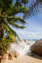 Breakers at the tropical beach with palms and granite rocks of la digue seychelles Royalty Free Stock Images