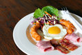 Breakfast with bacon, fried egg,sausages on grunge Royalty Free Stock Photo