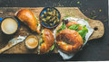 Breakfast with bagel, espresso coffee, capers on board, top view Royalty Free Stock Photo