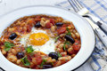 Breakfast beans with egg cannellini tomatoes black olives onion and parsley Stock Photography