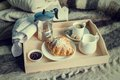 Breakfast in bed coffee croissant milk on tray wool blanket toned Stock Image
