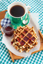 Breakfast with belgian waffles with jam and coffee on the tray on the checkered tablecloth top view Stock Image