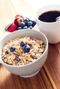 Breakfast bowl of muesli with fresh berries healthy on the table coffee cup straw and blue Stock Images