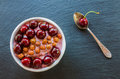 Breakfast bowl with yogurt,  granola or muesli or oat flakes, fresh cherries and nuts. Black stone background, top view Royalty Free Stock Photo