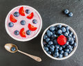 Breakfast bowl with yogurt, muesli, fresh blueberries and strawberries. Black stone background, top view Royalty Free Stock Photo