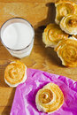 Breakfast with cinnamon buns and glass of milk on wooden table. Royalty Free Stock Photo