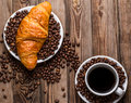 Breakfast coffee - cup and croissant with coffee beans on wooden background.