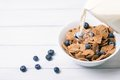 Breakfast with corn flakes with fresh berries and pouring milk on white wooden background. Selective focus and shallow depth of Royalty Free Stock Photo