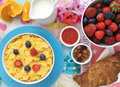 Breakfast with cornflakes, milk, croissants, jam, fresh fruits and almonds. Royalty Free Stock Photo