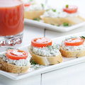 Breakfast of cottage cheese bruschettas and tomato juice sandwiches on white table Royalty Free Stock Images