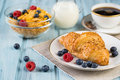 Breakfast with croissant cereal berries and fresh coffee on a light blue wooden background Royalty Free Stock Photos