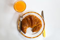 Breakfast with croissant and orange juice on dish Royalty Free Stock Images