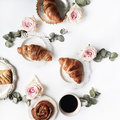 Breakfast with croissants, pink rose flower, petals, vintage plates and black coffee composition Royalty Free Stock Photo