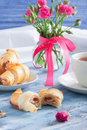 Breakfast with croissants tea and flowers on blue wooden tray. Royalty Free Stock Photo