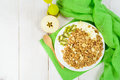 Breakfast with granola, fresh kiwi and apple on green tissue ove Royalty Free Stock Photo