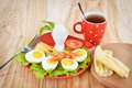 Breakfast with hard boiled eggs sliced in halves cup of tea salad tomatoes cheese and bread on the red plate wooden background Royalty Free Stock Photos