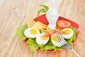 Breakfast with hard boiled eggs, sliced in halves, salad, tomatoes, cheese and bread on the red plate Royalty Free Stock Photo