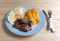 Breakfast meal on blue striped plate with fork and knife a of fried potatoes eggs strip steak a silverware atop a wood table in Stock Image