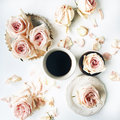 Breakfast with pink rose flower, petals, vintage plates, golden tray and black coffee mug composition Royalty Free Stock Photo