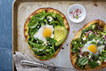 Breakfast pizza with baked egg and greens Royalty Free Stock Photo