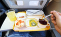 Breakfast in plane fruit small bun juice and tea passenger tries tea by teaspoon Royalty Free Stock Image
