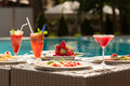 Breakfast by the pool light snacks fresh strawberries fruit smoothies Royalty Free Stock Photo