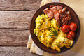 Breakfast is scrambled eggs with chives, fried bacon closeup. Ho Royalty Free Stock Photo