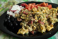 Breakfast scrambled eggs with olives tomatoes and radishes Stock Images