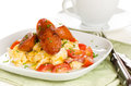Breakfast of scrambled eggs with tomatoes and chorizo sausage on white plate tea Stock Image