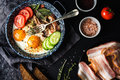 Breakfast set. Pan of fried eggs with bacon, fresh tomato, cucumber, sage and bread on dark serving board over black Royalty Free Stock Photo