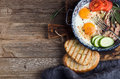 Breakfast set. Pan of fried eggs with bacon, fresh tomato, cucumber, sage and bread on rustic serving board over wooden Royalty Free Stock Photo