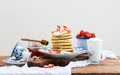 Breakfast set. Pancake tower with fresh strawberries, sour cream and honey on a porcelain plate over rustic wooden table Royalty Free Stock Photo
