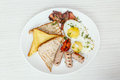 Breakfast setting with fried eggs, bacon, muesli, croissants and juice. Royalty Free Stock Photo