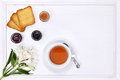 Breakfast table with tea cup of tea flower jam and bread on white Stock Photo