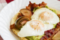 Breakfast tasty guacamole bacon and fried eggs Stock Photo