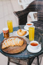 Breakfast for two persons on a balcony with beautiful view on the ocean fresh tea juice croissants jam and bread Stock Images