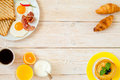 Breakfast on a white wooden background with plate with eggs and croissant Stock Photography