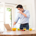 Breakfast and working portrait of young man using laptop while having Stock Image