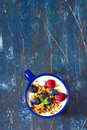 Breakfast yogurt witn granola and fresh berries on an old wooden board Stock Photos