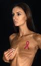 Breast cancer victim a female woman with has had a mastectomy medical procedure the lady is a survivor and has an awareness ribbon Stock Photography