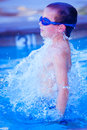 Breech boy freeze motion of a with goggles jumping out of a small pool Royalty Free Stock Images