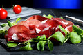 Bresaola on black stone carpaccio with arugula blue background Stock Images