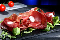 Bresaola carpaccio on black stone dark background Royalty Free Stock Images