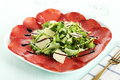 Bresaola with green salad and parmesan on white dish Royalty Free Stock Images