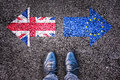Brexit flags of the united kingdom and the european union on asphalt road with legs Stock Photography