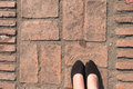 Brick block paving stone Floor texture. square shape Pavement patio and woman`s feet. Royalty Free Stock Photo