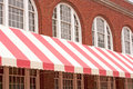 Brick building with striped awning old a pink and white Royalty Free Stock Photo