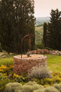 Brick-built well in tuscany garden Stock Photography